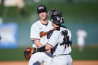 Oregon State Beavers relief pitcher Andrew Walling (40) is congratulated by catcher Cole Hamilton (14) after recording the final out of an NCAA game against the New Mexico Lobos at Surprise Stadium on February 14, 2020 in Surprise, Arizona. (Zachary Lucy / Four Seam Images)