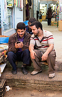 Fes, Morocco.  Young Men Checking a Cell Phone in the Medina.