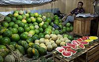 Yogyakarta, Java, Indonesia.  Man Selling Watermelons and Papayas, Beringharjo Market.