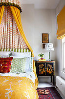 The bed is flanked by a pair of Chinese lacquered cabinets and dressed in a rich yellow fabric with matching blind and bed cover
