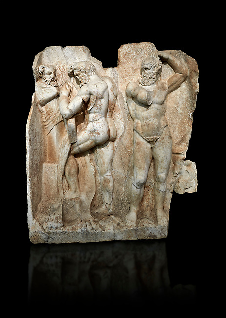Roman Sebasteion relief sculpture of  Herakles is preparing to wrestle the Libyan giant Antaios. Aphrodisias Museum, Aphrodisias, Turkey.  Against a black background.<br /> <br /> Herakles (left) is taking off his bow case to hang it on a pillar statue. Antaios (right) is binding up his head with ear protectors, next to him stands an oil basin used in the palaistra (wrestling ground). Antaios was a famous wrestler who challenged and killed all visitors to his country, until he was defeated by Herakles.