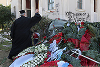 Pictured: A Greek Orthodox priest leaves a red carnation at the monument for the uprising at the Athens Polytechnic in Athens Greece. Thursday 17 November 2016<br /> Re: 43rd anniversary of the Athens Polytechnic uprising of 1973 which was a massive demonstration of popular rejection of the Greek military junta of 1967–1974. The uprising began on November 14, 1973, escalated to an open anti-junta revolt and ended in bloodshed in the early morning of November 17 after a series of events starting with a tank crashing through the gates of the Polytechnic.