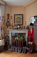 A collection of hunting and shooting gear on display around a fireplace; boots, a red coat and riding hat, a framed collection of ammunition, and Rosettes pinned to a curtain on the left