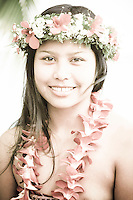 Local woman wearing haku head lei and orchid flower neck lei near ocean