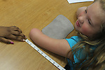 Students measure a young Waller student for a prosthetic hand and arm.