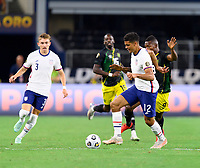 DALLAS, TX - JULY 25: Miles Robinson #12 of the United States and Cory Burke #9 of Jamaica chase after a loose ball during a game between Jamaica and USMNT at AT&T Stadium on July 25, 2021 in Dallas, Texas.
