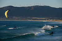 Spain, Andalusia, Tarifa, kite surfer at beach of atlantic ocean, behind wind farm on mountains