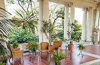 Wicker patio furniture on polished tile floor of luxurious outdoor room veranda of estate garden