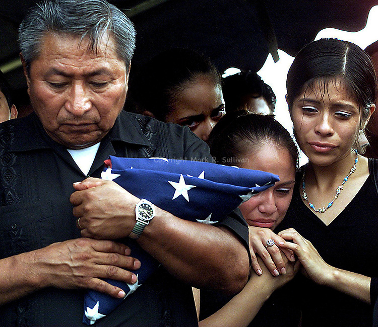 """""""FUNERAL""""<br /> <br /> Morners gather at the gravesite of Jose """"Eric"""" Solano who was murdered in a gang related shooting on Sat June 22 nd. Solano was an  by stander in a drive by shooting that occured on the corners of Suydam St & Joyce Kilmer Ave. Solano was buried at the St Peters Cemetery located on Rt 27 in New Brunswick. Here Jose's father (left) Jose Sp;ano holds the American Flag that draped his son's casket as two of the many morners grieve (right). Solano was a member of the New Brunswick High School's Jr. ROTC program and had planned on joining the Army after gradrating high school."""
