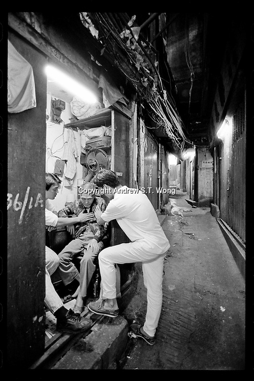 Hong Kong Chinese Christians pray for a sick elderly man at Kowloon Walled City in Hong Kong, 1987. Kowloon Walled City was a densely populated, largely ungoverned settlement in Kowloon, Hong Kong. Originally a Chinese military fort, the Walled City became an enclave after the New Territories were leased to Britain in 1898.