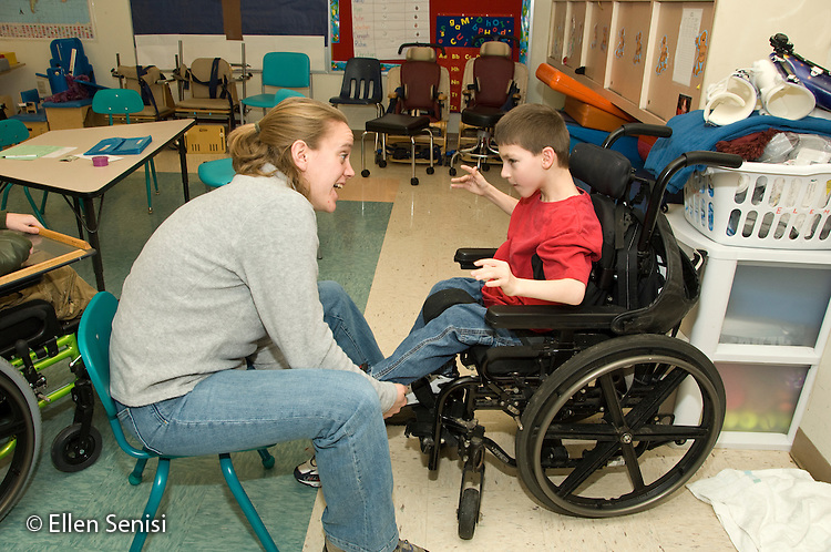 MR / Albany, NY.Langan School at Center for Disability Services .Ungraded private school which serves individuals with multiple disabilities.Teacher helps child put on AFO's (Ankle foot orthotics), as they interact. Boy: 9, cerebral palsy, limited verbal output with expressive and receptive language delays.MR: Ris4, Rub1.© Ellen B. Senisi