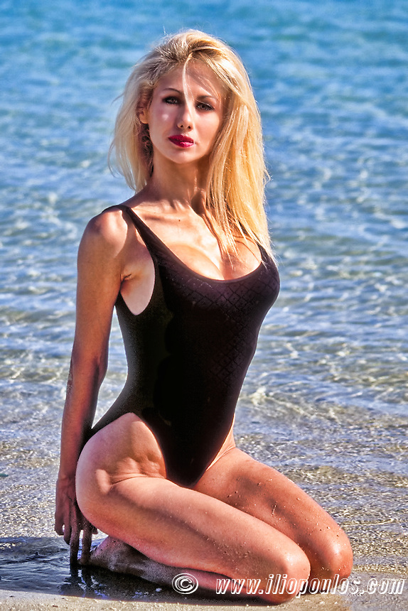 Beautiful young blond woman with swimsuit posing