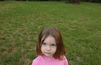 Girl in pink top stares at camera with green grass lawn.