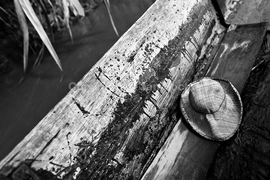 A crumpled hat of a Colombian sand miner is seen on the bottom of a wooden boat anchored close the bank of the river La Vieja in Cartago, Colombia, 10 December 2013. Artisanal (unmechanised) sand mining is an ancient mining technique used to obtain sand for construction purposes. Depending on the natural conditions (strength of the stream, depth of the river etc.), together with the sand miners' physical condition, the material is extracted in metal buckets, either by standing on the river bottom and searching for sand by feet, or, diving up to 3-5 meters deep using a wooden plank with steps. In spite of the physically demanding work, a sand miner's daily salary does not exceed 15-20 US dollars. However, the sand miners are very proud of their profession, valuing their work freedom above all, and usually, as long as their health and strength permit, they keep facing the river stream.