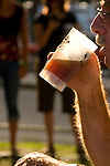 Male taking a sip of beer at the Oregon Brewers Festival, Portland, Oregon