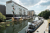 Construction of permanent moorings on the Grand Union canal in Hackney, overlooked by Hoxton Wharf apartment block in which rent for a one bedroom flat is £1625 a month. The number of houseboats on London canals has risen sharply as a result of rising rents and property prices.