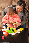 Two year old toddler boy with mother twisting turning block after mother showed him how it works, mother steadying piece for him