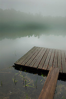 Wooden raft on foggy lake