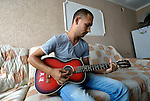 Elvis Ismili, a 24-year old Roma man in Suto Orizari, the Macedonian municipality that is Europe's largest Roma settlement, plays his guitar in his family's home.