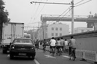 People cycling past a traffic jam along a city street, Beijing, China.