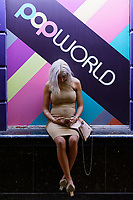 Pictured: A woman check her mobile phone outside Popworld in Wind Street, Swansea, Wales, UK. Saturday 07 August 2021<br /> Re: Nightclubs have reopened this weekend as most Covid restrictions have come to an end in Wales, UK.<br /> Pubs and restaurants were allowed to open for certain periods, with safety measures in place unlike nightclubs.