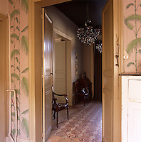 A view through a pair of yellow painted open double doors to a hallway beyond. The walls are papered in a leaf pattern wallpaper.