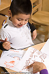 Education preschool 4 year olds art activity literacy hand of female teacher pointing to letter boy has written with a marker vertical