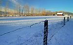 Idaho, North, Idaho Panhandle, Kootenai County, Blanchard. A farm and fence in a snowy landscape.