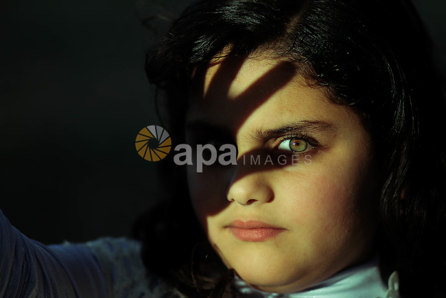 A girl with green eyes and shadows of her fingers on her face. Photo by Sanad Ltefa