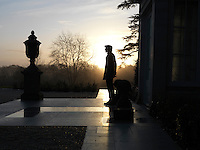 An antique stone urn is silhouetted against the trees and dramatic winter sunlight at the entrance to Limewood House in Hampshire