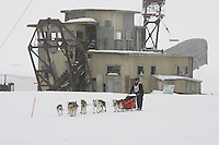 Paul Gebhart passes Swanberg's gold dredge on the trail nearing Nome in foggy conditions.    End of the  2005 Iditarod Trail Sled Dog Race.
