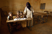 Girls are helped by their teacher in a classroom at the school in the village of Intedeyne. /Felix Features
