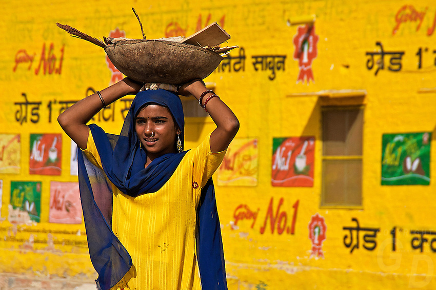 A Girl carrie her load in Bikaner a District in the northwest of the state of Rajasthan in northern India. The city is the administrative headquarters of Bikaner District and Bikaner division. It was formerly the capital of the princely state of Bikaner. The city was founded by Rao Bika in 1486 and from its small origins it has developed into the fourth largest city in Rajasthan. Just like Jaipur, Bikaner is called the Green City. .Bikaner Fort is popularly referred to as the Junagarh Fort. It was built by Raja Rai Singh who was one of Mughal emperor Akbar's trusted generals. There are as many as 37 citadels which protects the fort. This is one fort in Rajasthan which has never been annexed or conquered. There was one dubious instance though when Prince Kamaran laid seize to the fort, but could not keep it on hold for even 24 hours..