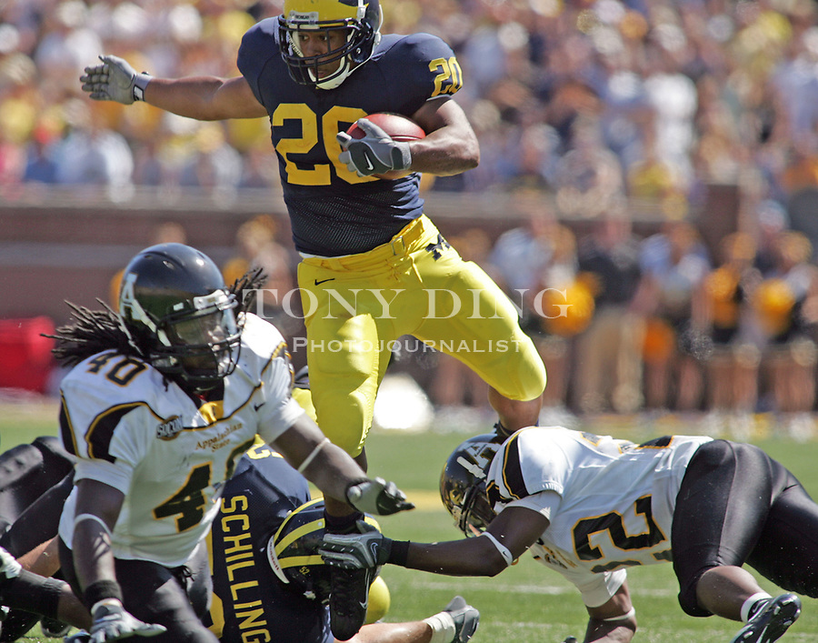 1 September 2007: Michigan running back Mike Hart (20) is tripped up by defensive back Leonard Love (22) in the 2007 season opener college football game between the Michigan Wolverines and Appalachian State Mountaineers at Michigan Stadium in Ann Arbor, MI. No. 5 ranked Michigan was upset 32-34.