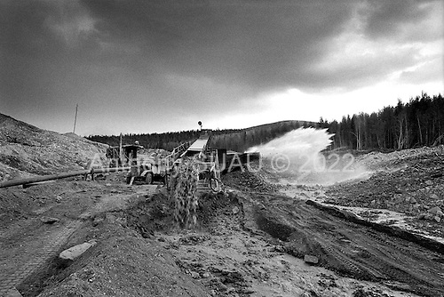 "Aldan, Yakutia, Russia  .May-June 1997.Stripping the river bed for gold in the southern region of Yakutia. The private company ""Seligdar"" uses a monitor/ water blaster to separate the gold from the earth. The environment in this region has been completely destroyed."
