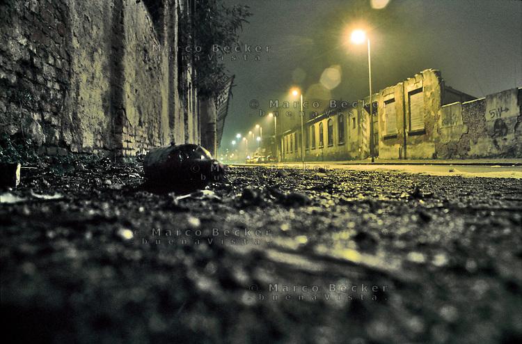 Milano, quartiere Bovisa, periferia nord. Una bottiglia a terra in via Bellagio, strada in stato di degrado che passa lungo vecchie fabbriche in disuso --- Milan, Bovisa district, north periphery. A bottle on the ground in Bellagio street, a road in a state of decay that runs along old disused factories