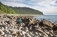 Hiker walks on the boulders of a rocky beach near Cape Fairweather in the Gulf of Alaska, Pacific ocean coast, Glacier Bay National Park, Southeast, Alaska.