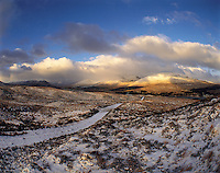 Mountain track leads across partly snow-covered moorland towards the cloudy hills of the Blackmount, Rannoch Moor, Scottish Highland