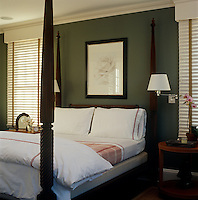 In an East Hampton bedroom fresh red and white checked and striped bedding is set off by olive green walls behind