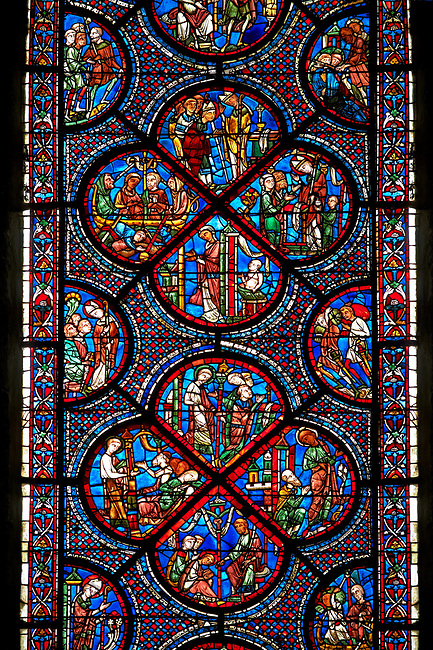 Bottom corners, left shows a belt seller, right a merchant. Centre panel, bottom shows a merchant with scales, left birth of St Nicholas, left the miracles of the first bath of St Nicholas, top The infant St Nicholas refuses his mother's milk except on mondays and fridays..Medieval Windows  of the Gothic Cathedral of Chartres, France, dedicated to the life an miracles of St Nicholas. A UNESCO World Heritage Site. .Bottom centre panel,  bottom shows The young St Nicholas does well at school, left Nicholas secretly gives gold to an old man to save his daughters , right The old man tries to thank Nicholas, who humbly flees from him, top .Nicholas is chosen to be the new Bishop ..Top centre panel, bottom shows The miracle of the boiling baby, saved by the intervention of St Nicholas, left An old couple's only son falls overboard en-route to the Saint's shrine, right The child lost at sea is found safe and well at the Saint's shrine, top Installation of Nicholas as Bishop of Myra