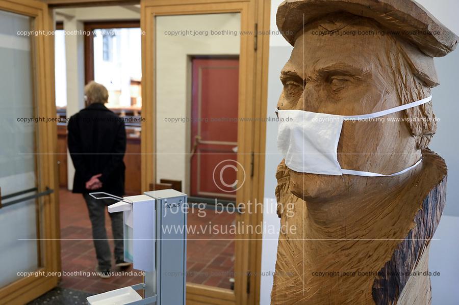 Deutschland, Hamburg, Christuskirche in Wandsbek, Reformator Martin Luther Skulptur aus Holz mit Mundschutz und Desinfektionsmittel in Zeiten der Corona Pandemie