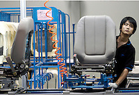 Workers at a Johnson Controls Plant work on the seat assembly line in Beijing, China..22-JUN-04