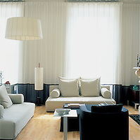 A stylish drawing room, with curtains in a voile by Baumann that filter the light through the Georgian windows, The sofas and side table are by Casamilano; the lights by Santa & Cole.
