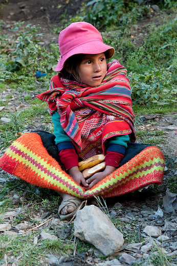 Hikers donate food to the children of Huilloc, as a thank you for welcoming them into the Andean community and teaching them about their weaving tradition and culture. The kids are pleased to be given these nutritious foods and appreciate the Backroads Active Travel group's company.