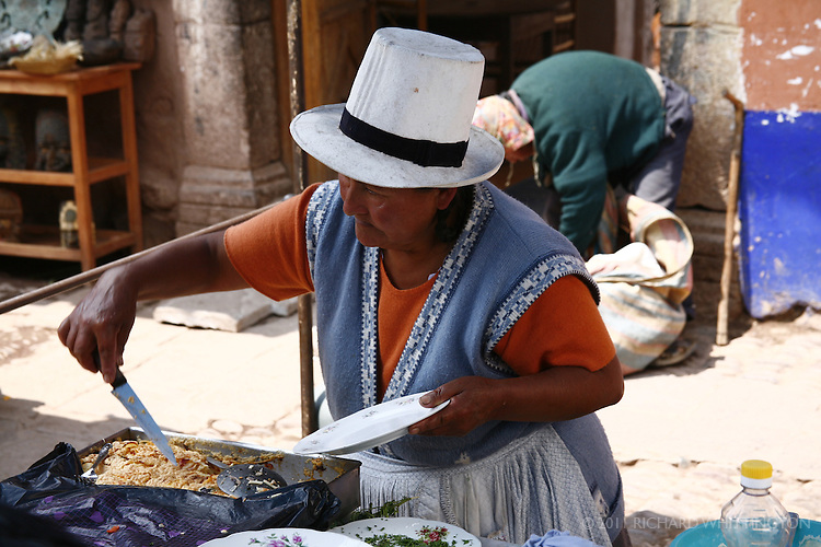 A Peruvian woman serves food at her house.