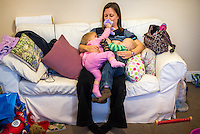 A mother breastfeeding her twin toddlers at the same time while sitting on a sofa in her sitting room. They are playing with each and with a stuffed toy animals while feeding.<br /> <br /> 16 November 2012<br /> Hampshire, England, UK