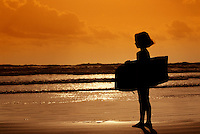 Girl with wave board looking out to the ocean.