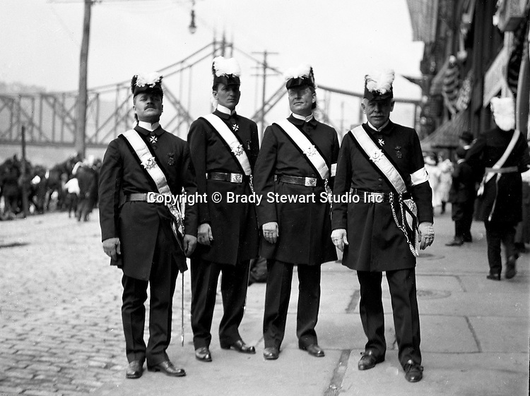 Pittsburgh PA: Homer Stewart (left) and brother Masons before the annual parade on Water Street. Wabash Railroad Bridge is in the background. Homer Stewart, Brady Stewart's father, was prominent in fraternal circles. He was a charter member of the Fort Pitt Lodge Free and Accepted Masons; Mount Moriah Council, Royal and Select Masters; 32nd-degree member of the Pennsylvania Consistory, Ancient Accepted Scottish Rite, Valley of Pittsburgh; and member of the Syria Temple, Ancient Arabic Order Nobles of the Mystic Shrine.