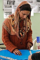 Dehradun, India.  Muslim Indian Woman Measuring a Piece of Fabric.