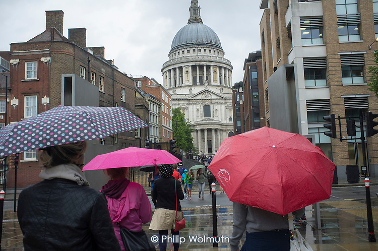 Tourists with umbrellas at St Pauls Cathedral London in heavy rain.